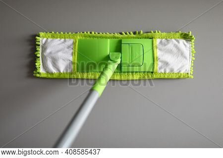Plastic Mop With Green Microfiber Cloth. Choosing A Mop For Home And Office Concept