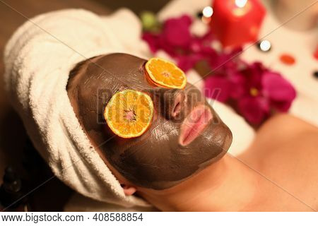 Portrait Of Woman With A Rejuvenating Face Mask And Orange Slices On Her Eyes. Facial Rejuvenation P