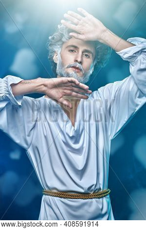 Divine man with a gray beard and curly  hair in a white tunic on a blue background with hearts. Art image of God. Roman and Greek mythology, Christianity and religion.