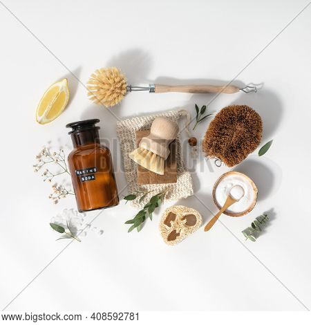 Eco friendly natural cleaning tools and products, bamboo and coconut dish brushes, luffa sponge, baking soda, lemon and solid soap on white background