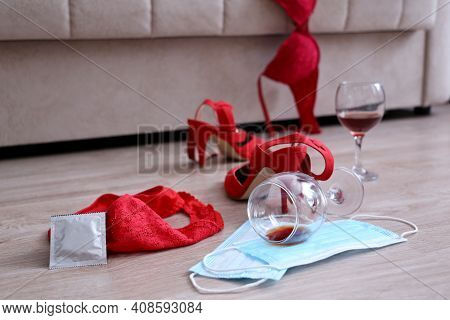 Sex On Quarantine, Two Medical Masks, Red Lace Lingerie, Wine Glasses And Shoes On A Floor Near Sofa