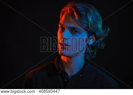Portrait of a handsome young man with wavy blond hair  in mixed color light on a black background. Men's beauty. Copy space.