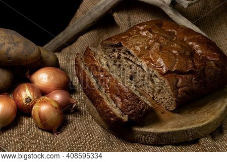 Black Bread And Vegetables On A Black Background. Borodino Bread. Homemade Baking. Bakery Product. P