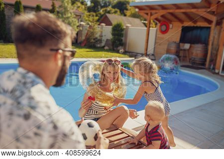 Parents Playing With Their Little Children By The Swimming Pool On A Hot Sunny Summer Day, Little Gi