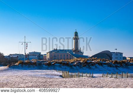 Lighthouse On Shore Of The Baltic Sea In Wintertime In Warnemuende, Germany.
