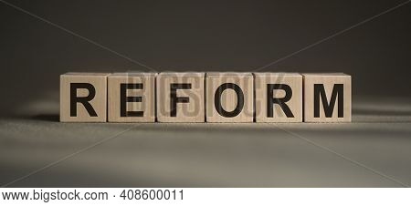 A Wooden Blocks With The Word Reform Written On It On A Gray Background.