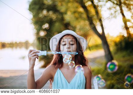 Portrait Of A Cheerful Girl Blowing Soap Bubbles. Happy Child  Plays Outdoors In Nature. Soft Focus.