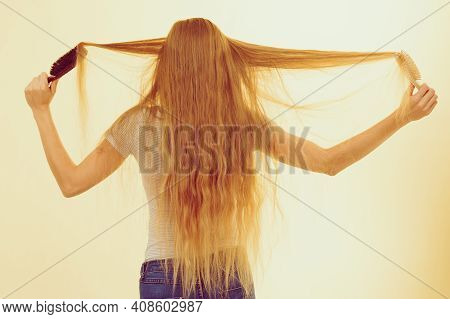 Blonde Woman With Brush Combing Her Very Long Hair. Teenage Girl With Bad Hair Care. Back View