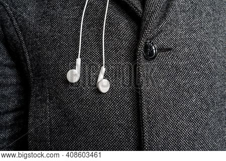 White Headphones On The Background Of A Man's Coat.