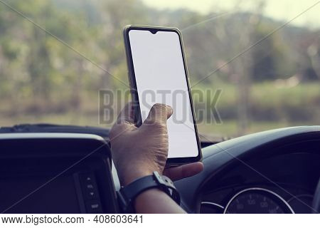 The Hand Of Driver Is Using A Mobile Phone To Help Navigate Or Gps While Parking On The Side Of The
