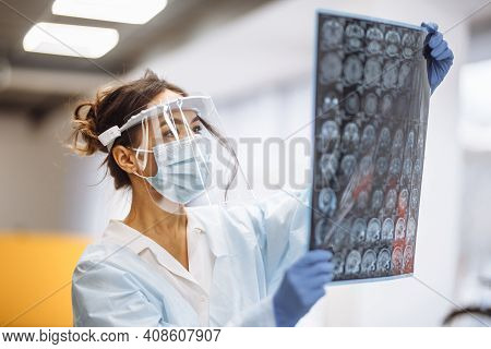 Woman Doctor Is Checking Brain Mri X-ray Image Of The Patient At The Hospital. Female Medical Worker
