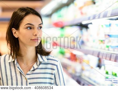 Closeup Portrait Of Millennial Female Customer In Supermarket. Young Woman Doing Grocery Shopping Lo
