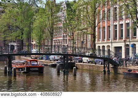 Amsterdam, Netherlands - July 10, 2017: People Visit Oudezijs Voorburgwal Canal In Amsterdam, Nether