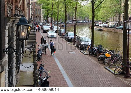 Amsterdam, Netherlands - July 10, 2017: People Stroll Along Herengracht Canal In Amsterdam City, Net