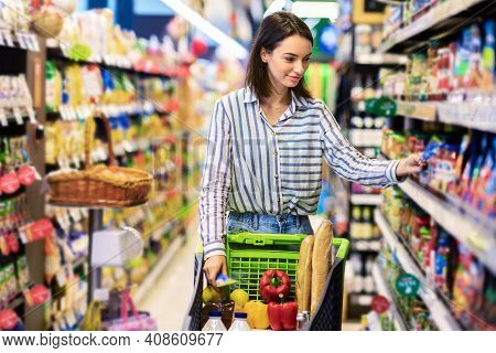 At The Supermarket. Portrait Of Young Woman Standing With Trolley Cart Between Aisles In Grocery Sto