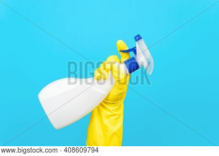 Hand In Yellow Glove Holding Cleaning Spray, Blue Background. Detergent Chemical For Washing Concept