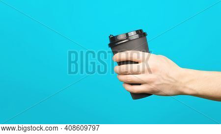 Male Hand Holding Disposable Cup Of Coffee On Blue Background, Copy Space. Takeaway Food Delivery Co