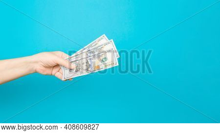 Female Hand Holding One Hundred Dollar Bills On Blue Background, Copy Space