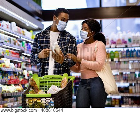 Young Black Couple In Protective Masks Shopping For Food Together At Supermarket During Covid Lockdo