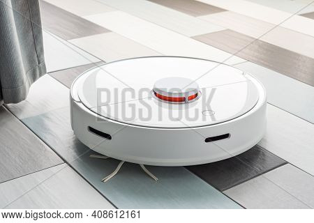 A Robot Vacuum Cleaner Helps In Cleaning An Apartment Or House. Autonomous Smart Technologies.