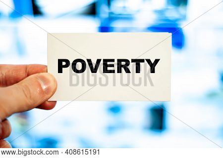 A Man Holds A Paper With The Word - Poverty On The Background Of The Monitor