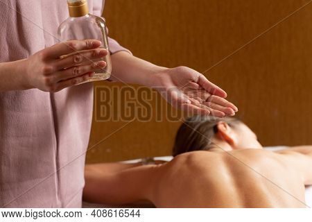 Masseuse Preparing For Doing Aromatherapy Oil Massage In Spa Salon. Close-up Of The Hands Of Masseus