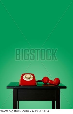 red landline rotary dial telephone, with its handset off the hook on a black wooden table, on a green background with some blank space on top
