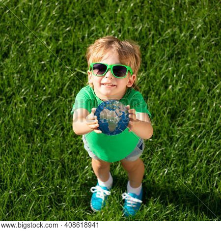 Child Holding 3d Planet In Hands Against Green Blurred Background. Earth Day Spring Holiday Concept.