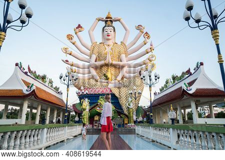 Koh Samui, Thailand - January 10, 2020: Woman In A Red Dress Standing In Front Of Statue Of Shiva In