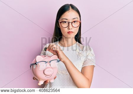 Young chinese woman holding piggy bank with glasses relaxed with serious expression on face. simple and natural looking at the camera.