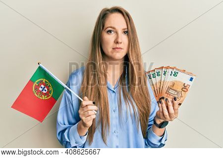 Young blonde woman holding portugal flag and euros banknotes relaxed with serious expression on face. simple and natural looking at the camera.