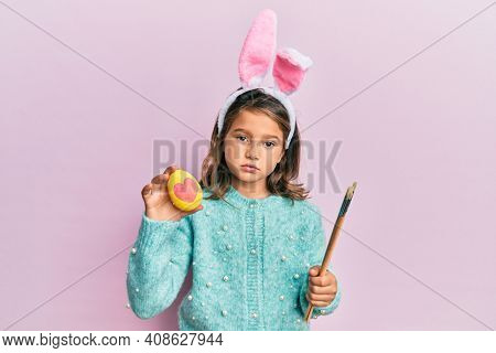 Little beautiful girl wearing cute easter bunny ears holding colored egg relaxed with serious expression on face. simple and natural looking at the camera.