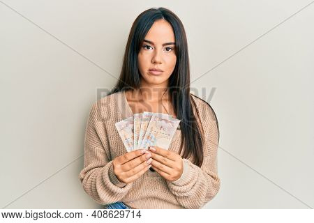 Young beautiful hispanic girl holding 10 united kingdom pounds banknotes relaxed with serious expression on face. simple and natural looking at the camera.