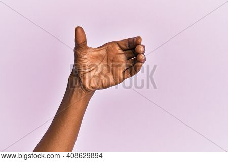 Arm and hand of black middle age woman over pink isolated background holding invisible object, empty hand doing clipping and grabbing gesture
