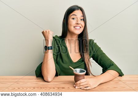 Young brunette woman drinking mate infusion screaming proud, celebrating victory and success very excited with raised arm