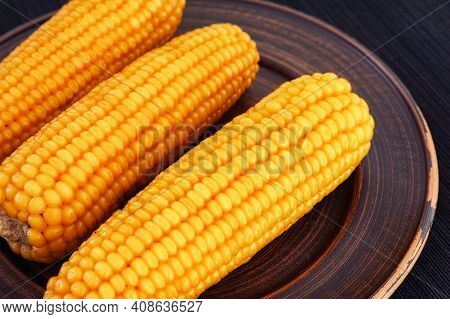 Boiled Corn Cobs On A Plate. Low Key. Close Up.