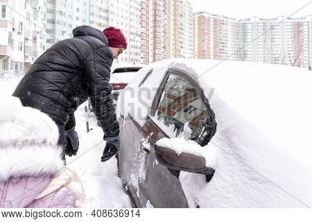 Young Man Clears Snow From His Car. Car In The Snow After A Night Blizzard