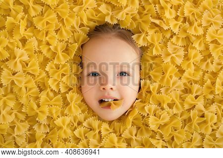 A Large Pile Of Pasta In The Form Of A Bow. The Child Eats Pasta. Pasta Made From Durum Wheat. The B