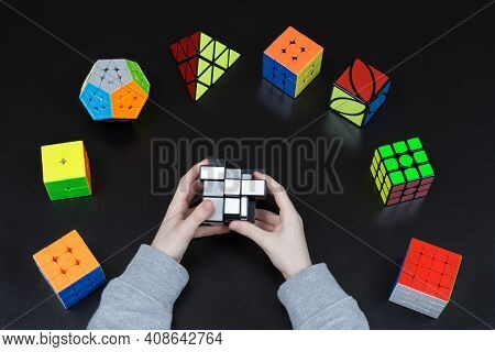 Dnipro, Ukraine - May 11, 2020 - Boy Solving Mirror Cube. Collection Of Cubes On The Table (4x4x4 3x