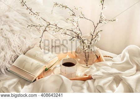 The Atmosphere Of A Romantic Morning, Coffee In Bed. Flowering Branches In A Vase, An Open Book And