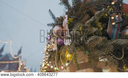 Close-up Of Decorations On City Christmas Tree. Action. Bottom View Of City Christmas Tree With Deco