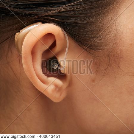 Hearing Aid Behind The Ear Woman, Close-up, Side View. Deafness Treatment, Hearing Solution