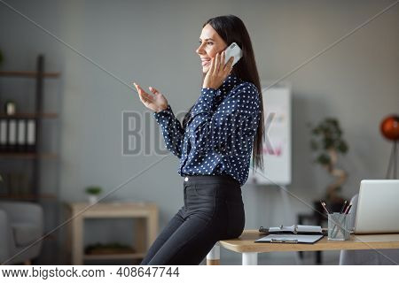Profile Side Photo Of Attractive Young Woman Sit On Table Talk Smartphone Client Indoors Workplace I