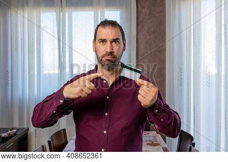 Bearded Man In A Purple Shirt Pointing Worriedly At A Credit Card. Worry Concept