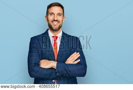 Handsome man with beard wearing business suit and tie happy face smiling with crossed arms looking at the camera. positive person.