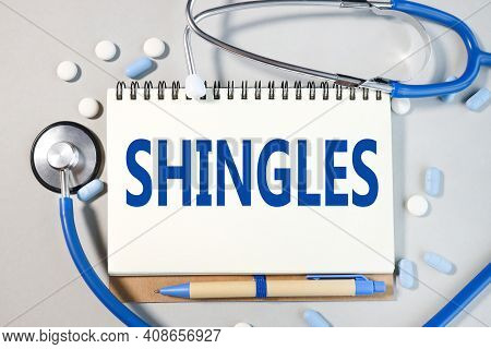Shingles . Text On White Paper On Gray Background. Notepad Near Blue Stethoscope And Pills