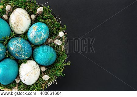 Easter Background With A Nest With Colored Eggs Close-up On A Black Background With Copy Space. Turq