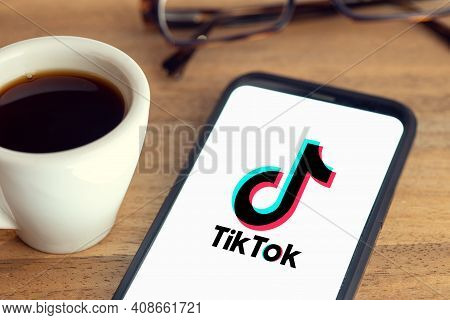 Galicia, Spain; February 15, 2021: Tik Tok Logo On Smart Phone Screen On Desk With Eyeglasses And Cu