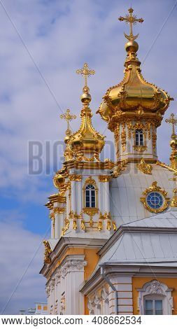 Church with golden domes against a clear blue sky on a sunny day. Orthodox cross on the dome of the church against the blue sky. St. Petersburg, Petrodvorets.