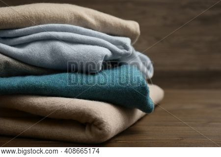 Stack Of Cashmere Clothes On Wooden Background, Closeup